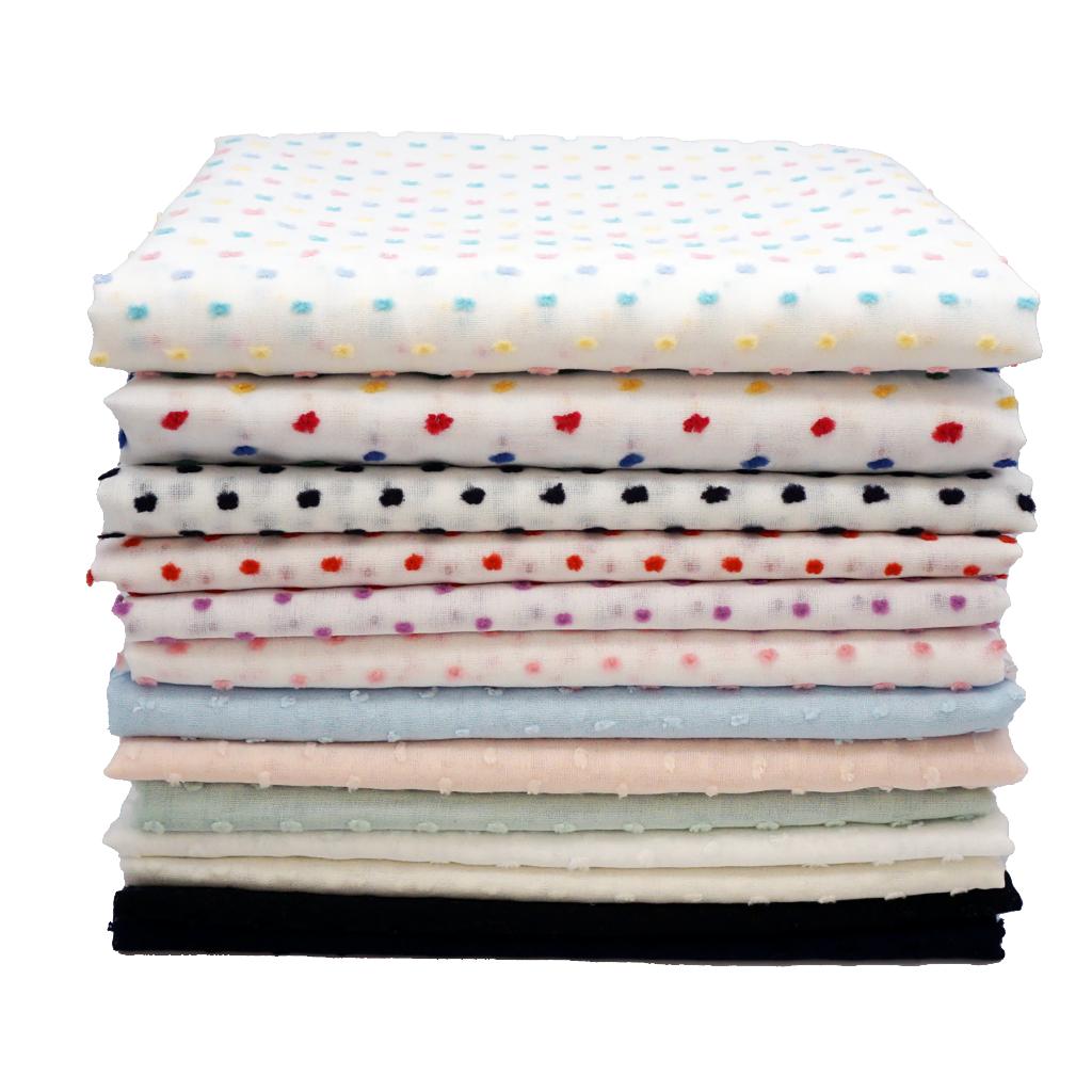 stack of folded cotton swiss dot fabrics product photo